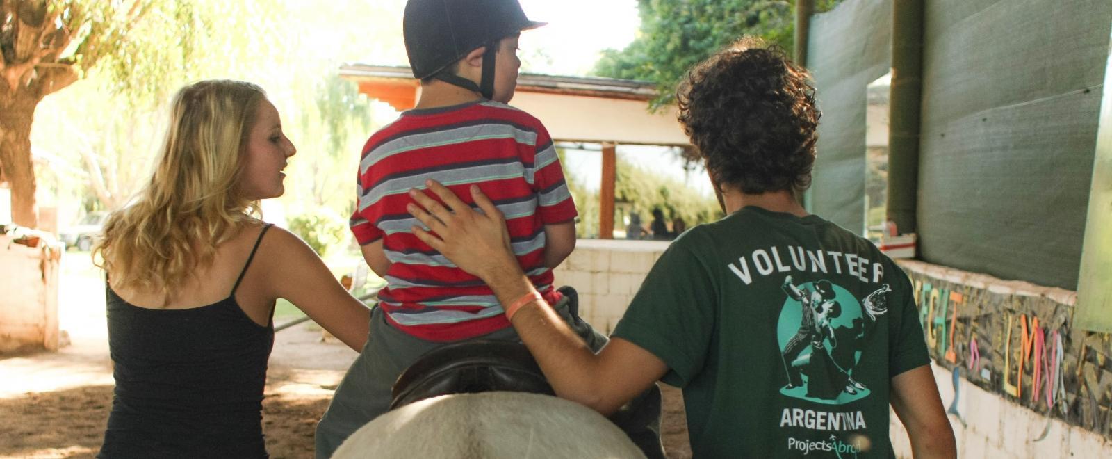 Voluntarios de Equinoterapia ayudando a un niño con síndrome de Down a montar un caballo.